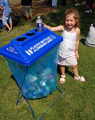 Young girl placing bottle in recycling container