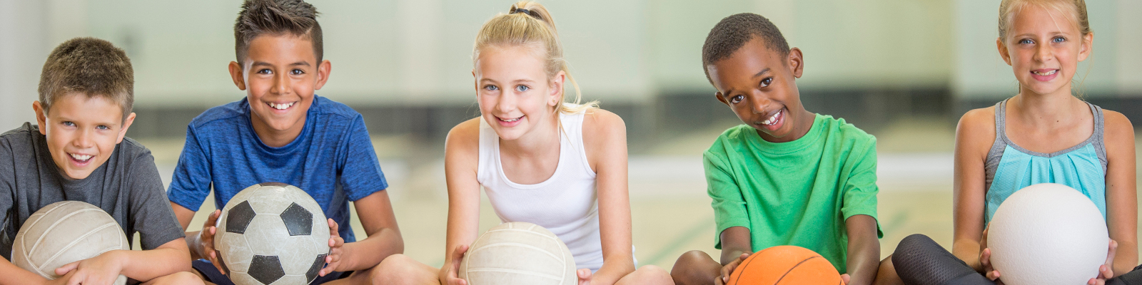 Children sitting on a gym floor with different sports balls