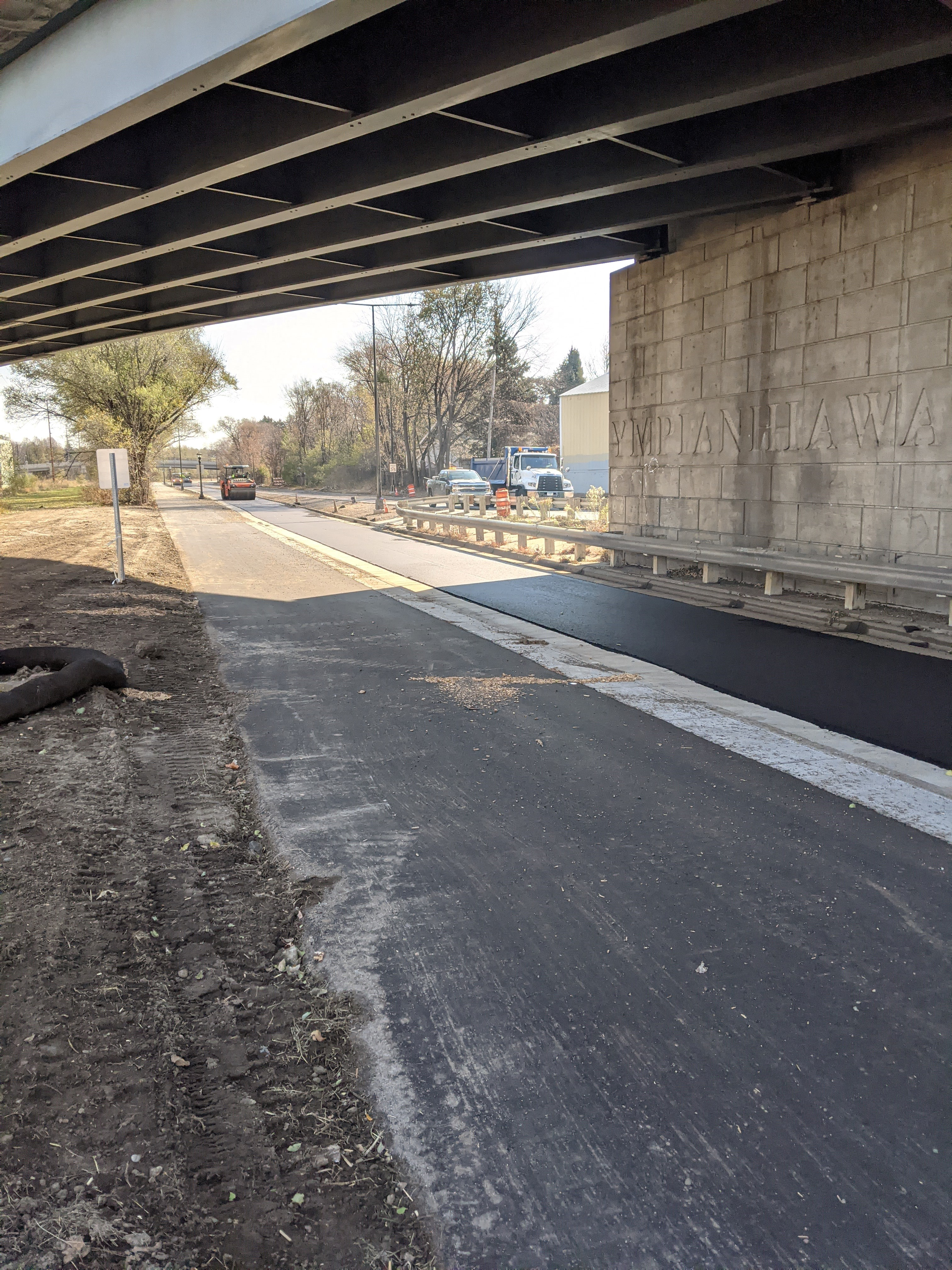 Photo of Ayd Mill Road construction. The photo shows the view facing southbound from under the Selby Avenue overpass from the new trail.  Steel drum roller is compacting freshly placed asphalt on northbound lane.