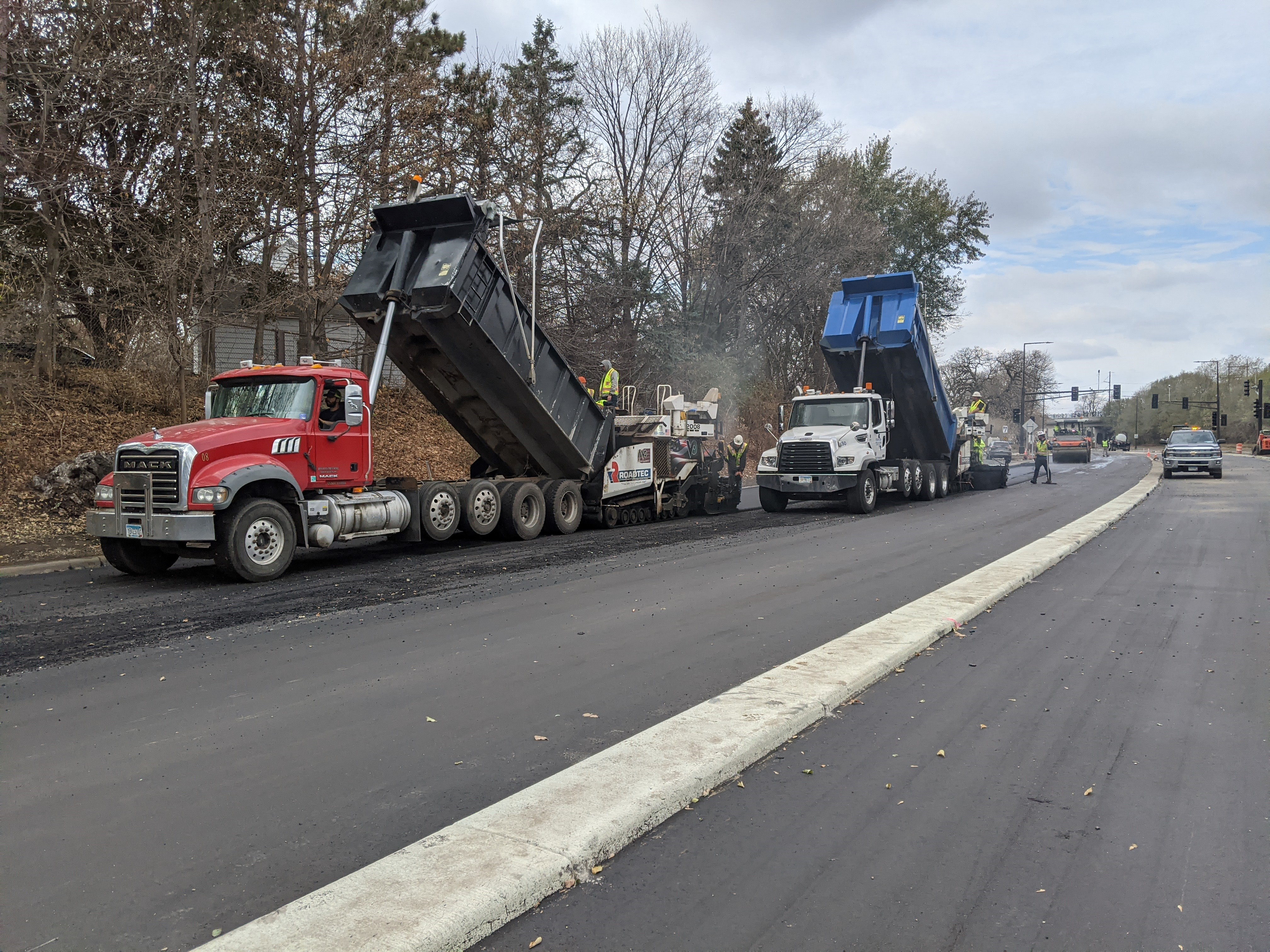 Construction photo of Ayd Mill Road from 11.2.20. Photo shows the view from northbound Ayd Mill Road between the Summit Avenue bridge and Ashland Avenue. In the photo, the contractor is paving southbound lanes of Ayd Mill Road using large equipment.