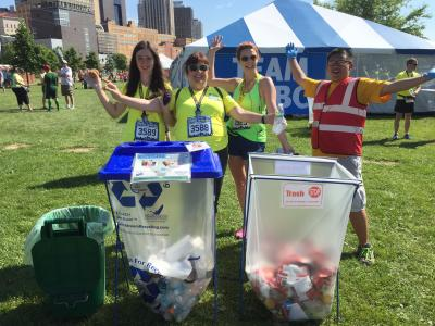 Individuals standing next to recycling and trash containers at an event outdoors