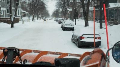 "View from a snow plow looking at a residential street before doing ""pushbacks"" and plowing efforts to clean up extra snow and ice."
