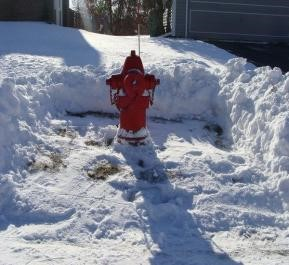 Fire hydrant shown in winter with immediate area cleared of snow.