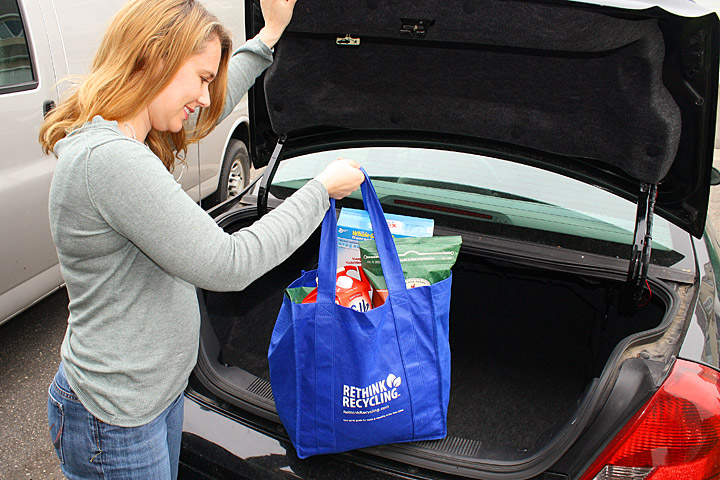 woman loading groceries into her trunk using a reusable grocery bag