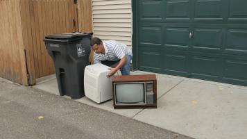 Man setting a TV next to his garbage cart.