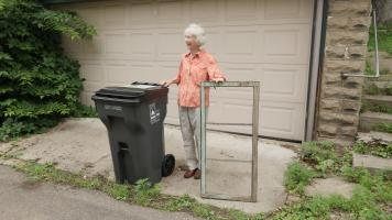 Photo of a woman placing a window next to her garbage cart.