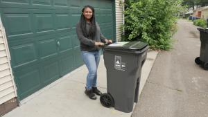 Image of a girl standing with a garbage cart, button link to information about citywide garbage service.