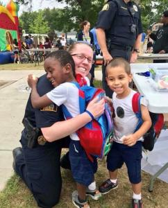Police Officer and kids hugging at Safe Summer Nights