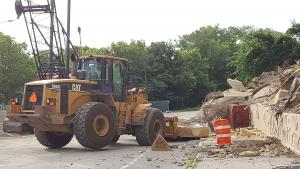 pw - excavator removing a large limestone slab from Wabasha Street
