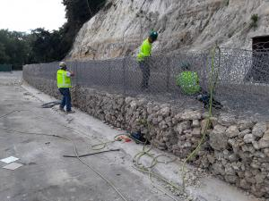 Contractors with wire cages building the gabion wall on Wabasha