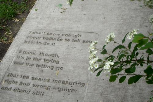 Stamped poem in Saint Paul Sidewalk that reads: I don't know enough / about balance to tell you / how to do it / I think, though, / it's in the trying / and the letting go / that the scales measuring / right and wrong - quiver / and stand still