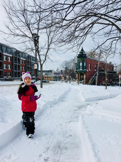 Girl walking along sidewalk on a snowy day