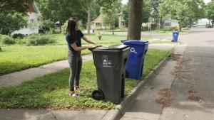 Picture of a woman placing a garbage cart out at the curb.