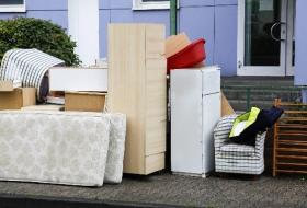 Image of bulky items set out for garbage collection. Chair, Refrigerator, Mattress, Electronics.